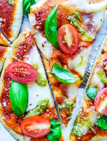 The best, easy homemade Margherita Naan Pizza Recipe! The recipe uses naan bread, tomatoes, mozzarella cheese, fresh basil, and basil pesto and is ready in under 15 minutes making it the perfect weeknight dinner recipe for families. Bonus is this recipe is freezer friendly and makes great leftovers. Simple step by step instructions and VIDEO! #pizza #recipe #easyrecipes #dinner #margheritapizza #weeknightdinner