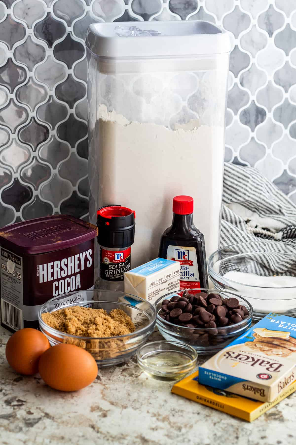 Brownie ingredients laid out on white counter in containers and small bowls.