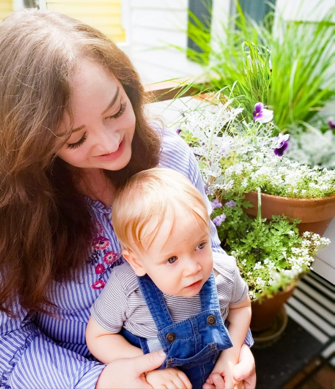 Image for About Me section showing Caitlyn holding a toddler with flowers in the background.