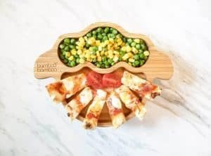 Naan pizza sticks with peas and corn on a bamboo bamboo sheep plate.