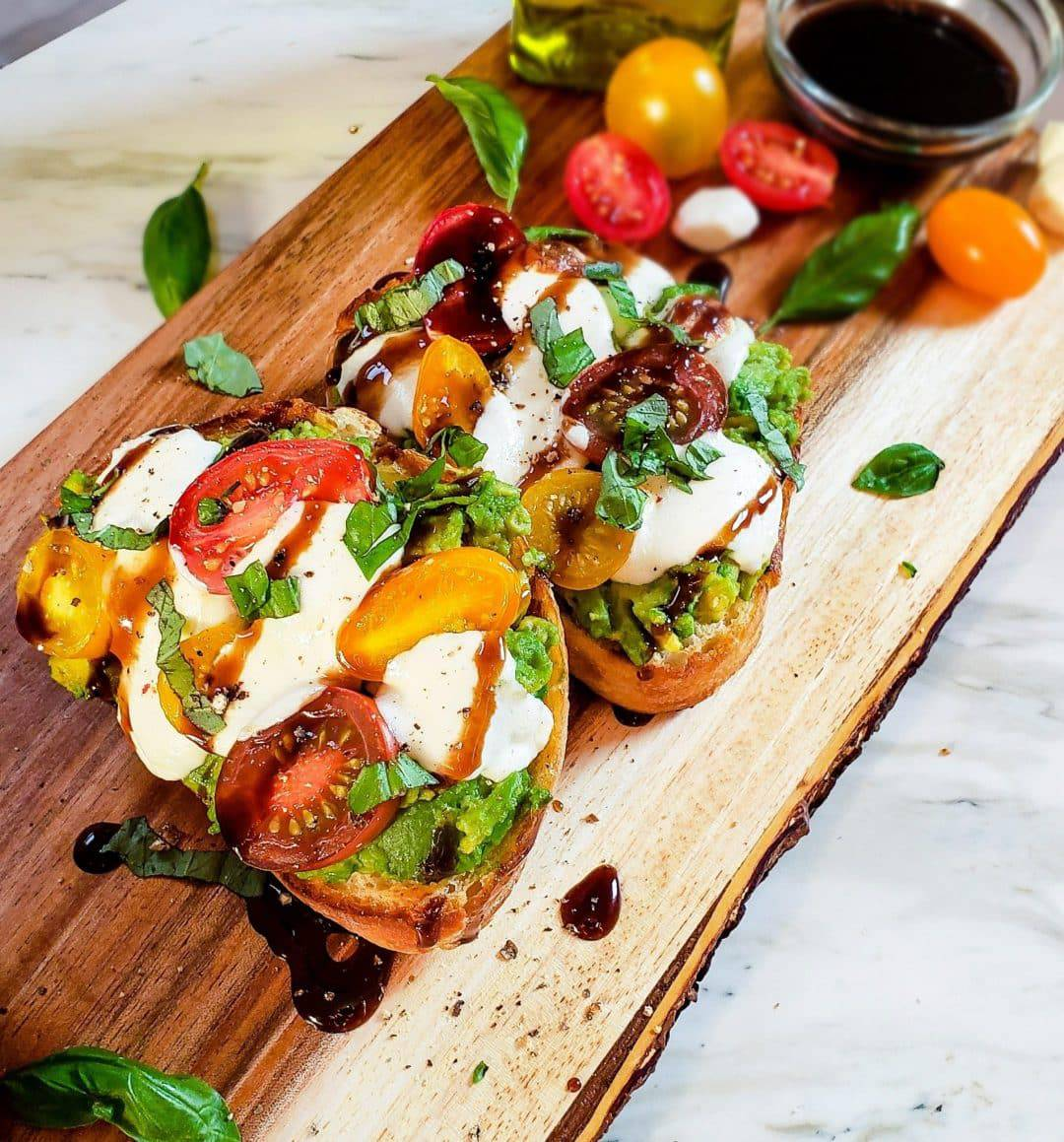 A picture of caprese avocado toast. There are two pieces of toast with mashed avocado, cherry tomatoes, mozzarella, balsamic glaze and fresh tomatoes on top.