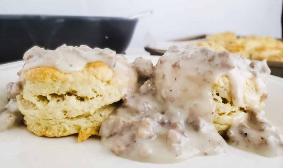 Picture of Southern biscuits and sausage gravy on a white plate. There are two biscuits on the plate with the gravy covering them There is the rest of the biscuits and gravy in the background blurred out.