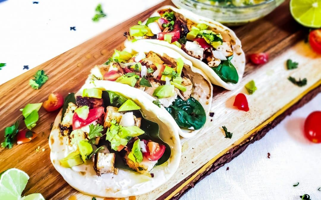 Grilled Chicken Street Tacos on a wooden cutting board. There are three tacos in the picture and they all have tomatoes and avocado on them. Surrounding the tacos is limes, tomatoes, and cilantro. In the background is a bowl of cilantro lime butter blurred out.