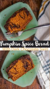 """Pin for the pumpkin spice loaf cake recipe. The picture is the same as the featured image. It has two pieces of bread on glass teal plates on a wooden surface. On the right there is a white, blue and yellow plaid towel and the top plate has a silver fork. In the middle is black and orange text saying """"pumpkin spice bread with dark chocolate swirl"""""""