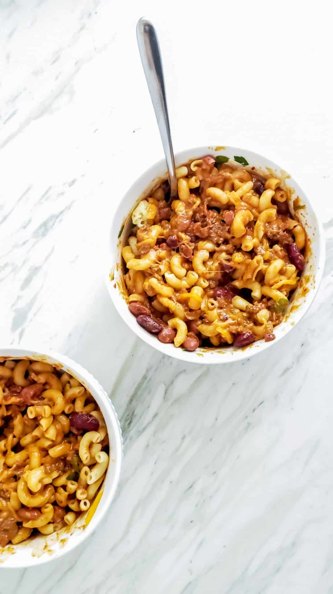 Two small bowls of stirred sweet and spicy chili mac and cheese. The bowls are white and on a marble table. The top bowl has a silver spoon in it.