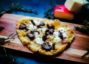 Vegetarian Flatbread Pizza on a wooden cutting board. The pizza is topped with 3 types of cheese, mushrooms, sun-dried tomatoes and fresh rosemary. The pizza is surrounded by rosemary and has cheese blocks in the background. All of this is on a blue counter top.