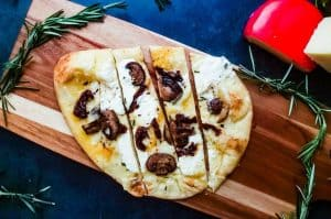 An overhead shot of the Vegetarian Flatbread Pizza recipe. The pizza is on a cutting board on a blue counter top and surrounded by fresh rosemary and 2 cheese blocks.