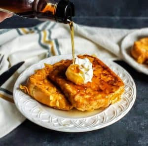 French toast on a white plate with syrup being poured on top.