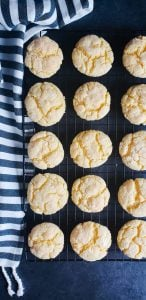 Image is for gooey butter cake cookie recipe. These St. Louis style cookies are on a cooling rack lined up 5 by 3. The rack is sitting on a blue counter top and there is a blue and white striped image on the left side.