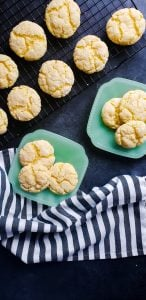 Overhead image for gooey butter cake cookies recipe. Cookies are on wire cooling rack. There are also 2 teal plates with 3 cookies each on them There is a blue and white towel at the bottom.