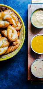On the right center part of the image is a woven basket filled with homemade soft pretzels. The basket is cream and yellow and only half can be seen in the photo. On the right side is the pretzel cheese sauce trio recipe. The bowls are cream, white and green and in a vertical line on a wooden tray with gold handles. All of this is on a blue counter top.