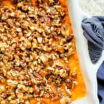 Overhead shot of sweet potato casserole in a white baking dish on a white counter.