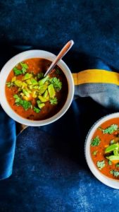 Image for vegan black bean soup recipe. The image is of two white bowls filled with soup. The bowls are on a navy blue counter and the top bowl on the left has a spoon in it. The bottom right bowl is halfway out of frame. The bowls are surrounded by a blue, yellow, and gray towel.