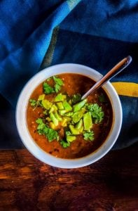 Close up above the head shot of vegan black bean soup recipe. The soup is in a white bowl with a silver spoon sticking out. The soup is topped with avocado and cilantro. The bowl is on a wooden surface with a blue, gray and yellow towel on the top half of the photo. The bowl is fully in focus in the middle of the photo.