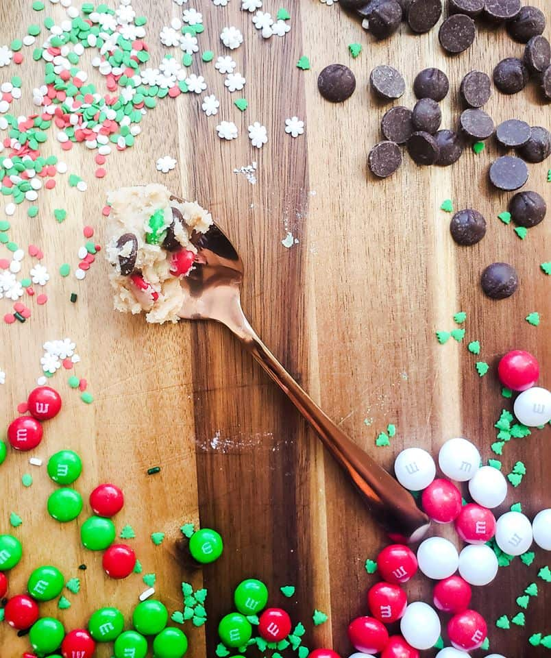 Overhead shot of cookie dough on a gold spoon with candy, sprinkles and chocolate surrounding it.