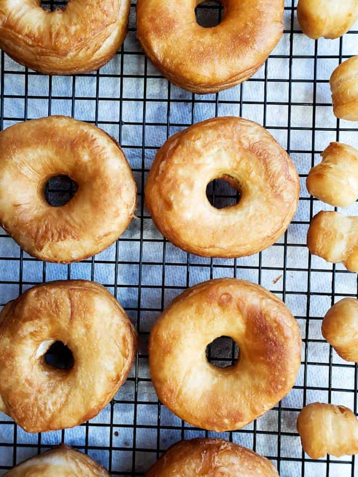 Plain donuts on a cooling rack.