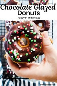 "Pin image for Chocolate Glazed Donut Recipe, The image is of a hand holding a donut strait on and center. In the background you can see more donuts on a sire cooling rack. On the bottom there is a blue and white striped towel. On the upper part of the photo in black writing are the words ""Chocolate Glazed Donuts: Ready in 15 minutes"". The shot is taken from above."