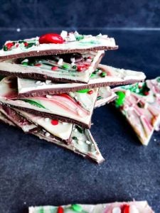 Image for Christmas chocolate bark recipe, The image is taken at a angle and shows the bark stacked on top of each other on a blue counter.