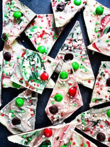 Overhead shot for Christmas Chocolate Bark recipe. The image shows the bark on a blue counter sliced and randomly stacked on each other.