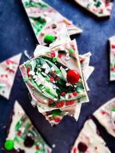 Christmas chocolate bark stacked on top of each other on a blue counter top.