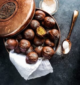 Image for gingerbread truffles recipe. the image is shot from above. In the center it shows a copper tin of truffles with one of the truffles having a bite out of it. Next to the tin is a copper spoon and small bowl of spiced sugar.