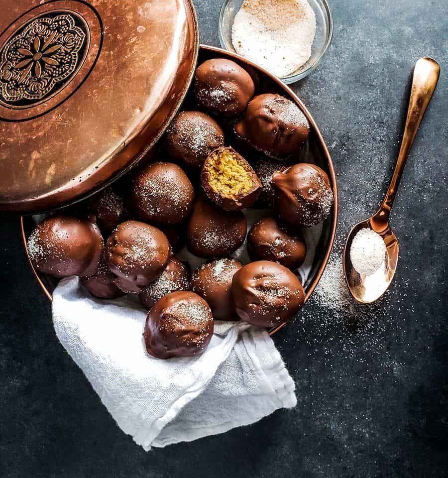 Gingerbread truffles in a copper tin with gold spoon on the right.