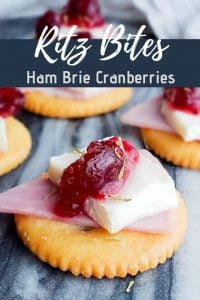 "Pin for Ritz Bites with Ham, Brie and Cranberries Recipe. This image shows a close up of a bite on a blue marble surface. There are other bites blurred out in the background. Near the top is the words ""Ritz Bites, Ham Brie Cranberries""in white writing."