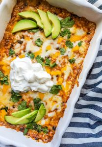 Overhead image for chicken enchilada dip. The dip is in a white baking dish and topped with sour cream, avocado, and cilantro.