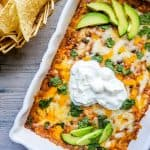 The BEST Baked Chicken Enchilada Dip recipe! This Mexican inspired appetizer is super easy and cheesy and filled with beans, corn and tons of flavor. Top with avocado, sour cream and cilantro for the perfect finish!