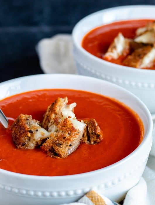 The best soup recipe for the cold weather months! This Roasted Red Pepper Tomato Soup is super healthy, vegan, and dairy free. An added bonus is that this recipe is easy and ready in only 30 minutes for busy weeknight dinners. Pair with fresh basil, croutons, or is you aren't vegan grilled cheese bites for the perfect finish. #tomatosoup #healthy #vegan #dairyfree #30minutemeal