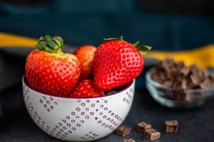 A white bowl of strawberries with a bowl of chocolate chips in the background blurred out. These both are sitting on a dark blue counter. In the background is blue and yellow.