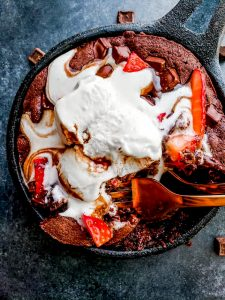Overhead shot of mini skillet brownie with strawberries and vanilla ice cream on top.