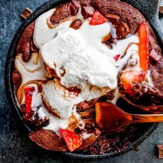 This Skillet Brownie Sundae for Two is the perfect date-night dessert for Valentine's Day! This recipe combines chocolate, ice cream, hot fudge and strawberries in a tiny iron skillet for the perfect indulgent treat! #ValentinesDay #Dessert #Brownie #ForTwo #SmallBatch