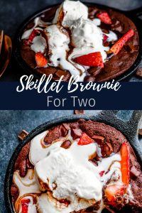 """Pin image for Skillet Brownie recipe. Top image shows the brownie in an iron skillet sitting on a dark blue counter. The brownie is topped with melting ice cream, strawberries and for fudge. The bottom image is an above shot of the same brownie in a skillet close up. In the center is white text saying, """"skillet brownie for two""""."""