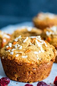 Close up shot on one single muffin. The muffin is centered and there are muffins blurred out in the background. The muffin is sitting on a white piece of parchment paper and the background is dark blue.