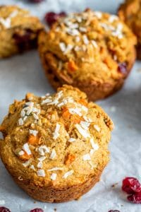 The image shows the muffins on parchment paper. The image is shot from 45 degrees and shows two muffins focused on the tops with some blurred out in the background.