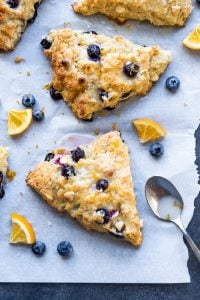 Blueberry white chocolate scones on a piece of parchment with blues lemon slices.