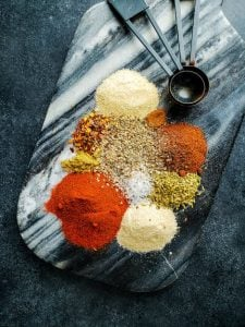 Image of all Mexican Spices on a blue and white marble cutting board.