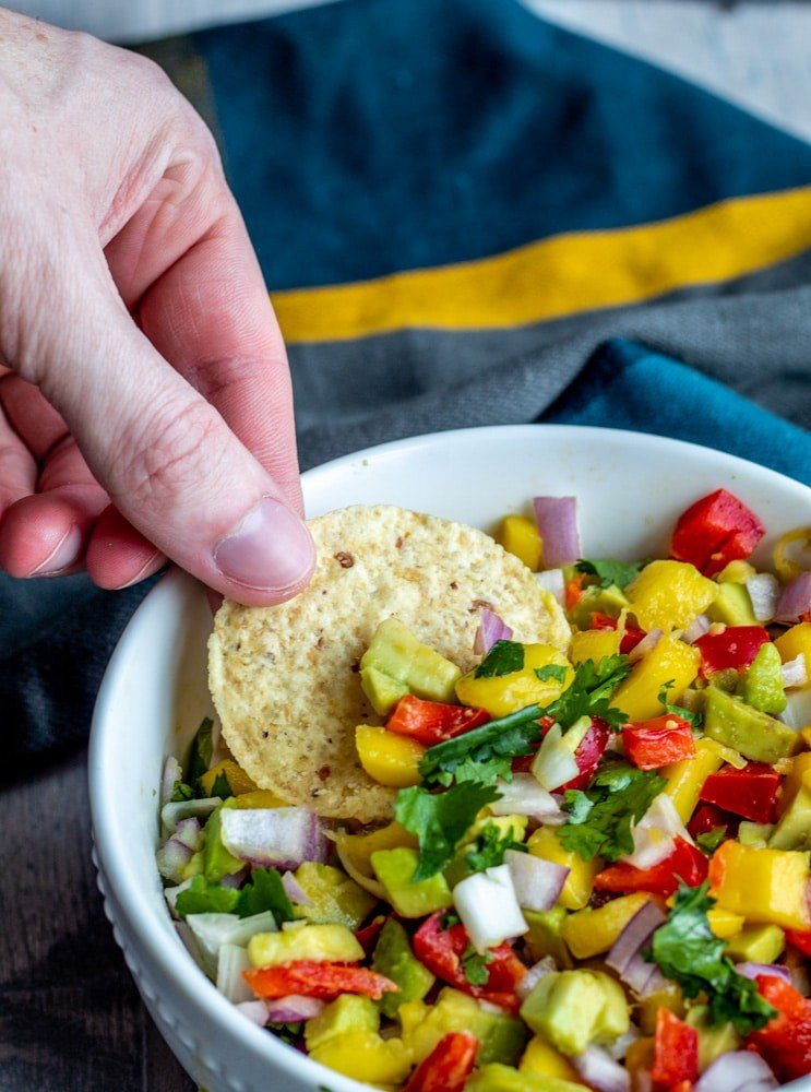 Hand dipping chip  into bowl of salsa.