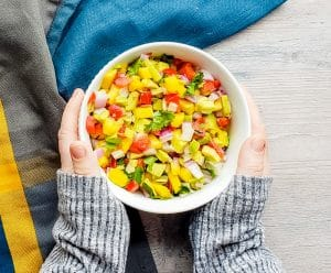 Salsa in a white bowl with two hands holding it.