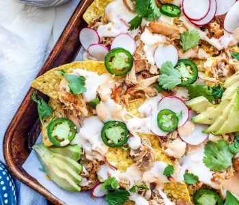 These sheet pan pork carnitas nachos with homemade queso are perfect for a quick and easy weeknight dinner, parties, holidays, or game days! Top with fresh cilantro, jalapeno, and lime for the best finishing touch! #nachos #MexicanFood #pork #food