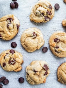 Baked cookies on a piece of parchment paper with chocolate chips around them.