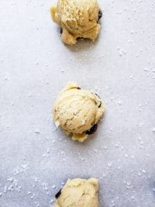 Overhead shot of raw cookie dough in a line on parchment paper.