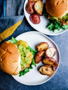 Overhead shot of two grilled chicken burgers on their own white plate with red potatoes.