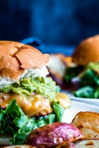 Close up shot of grilled chicken burger with another in the background blurred out.