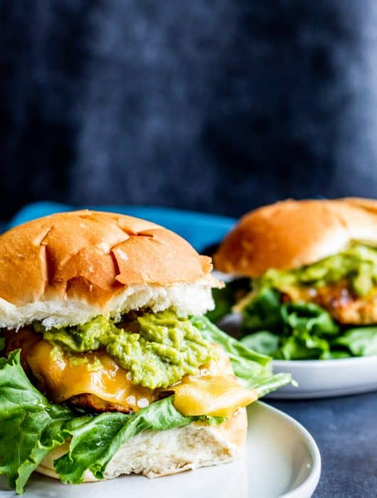 These Grilled Chicken Burgers with Guacamole and Garlic Aioli are the best summer grill burger for the entire family. The meat is juicy and filled with flavor and pairs perfect with store bought or homemade guacamole, Gouda cheese, lettuce and homemade garlic aioli. Don't have a grill? No problem, make on the stove top as well! #burgers #grilling #food #recipe #chicken