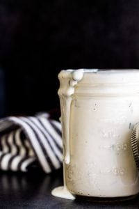 Buttermilk ranch dressing in a glass mason jar spilling over the side on a dark blue counter.