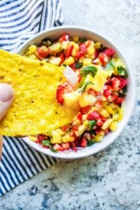 Tortilla chip being held with salsa on it and white bowl blurred underneath.