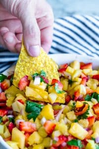 Hand reaching into strawberry pineapple salsa with a tortilla chip.