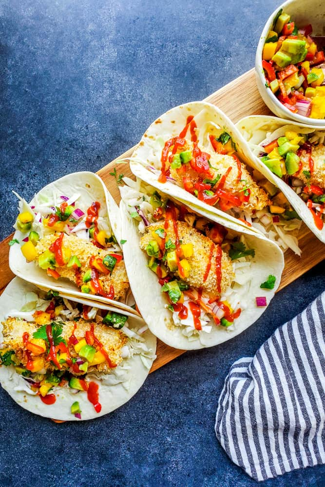 These Baked Coconut Crusted Healthy Fish Tacos with Mango Avocado Salsa is the best, easy recipe for a quick under 30 minute family weeknight dinner! The cod is baked in the oven until crispy, then paired with cilantro lime cabbage slaw for the perfect finish. {VIDEO} #fish #food #healthy #bakedfish #tacos